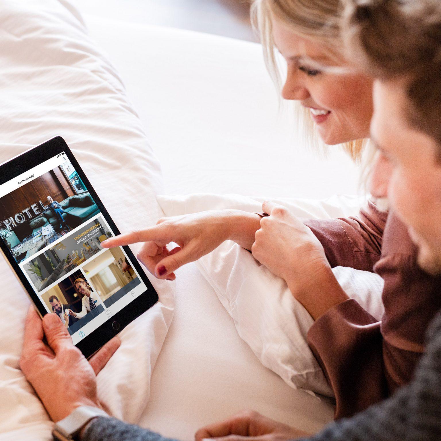Ein Pärchen nutzt die Digitale Gästemappe von Gastfreund auf einem Tablet
