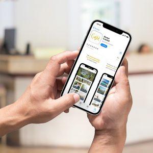 Ein Smartphone zeigt den App Store Eintrag einer gebrandeten Hotel-App von Gastfreund