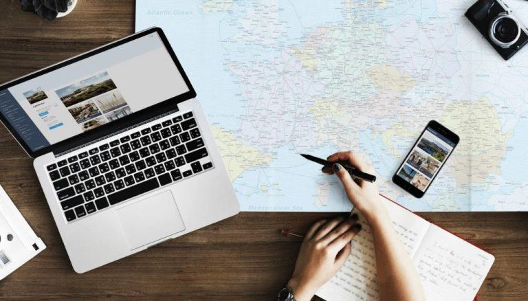 Ein Schreibtisch mit Laptop, Reisekarte und Digitaler Gästemappe von Gastfreund auf einem Smartphone