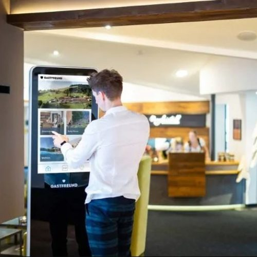 Touchscreen-Kiosk von Gastfreund präsentiert Digitale Gästemappe neben der Rezeption im Hotel