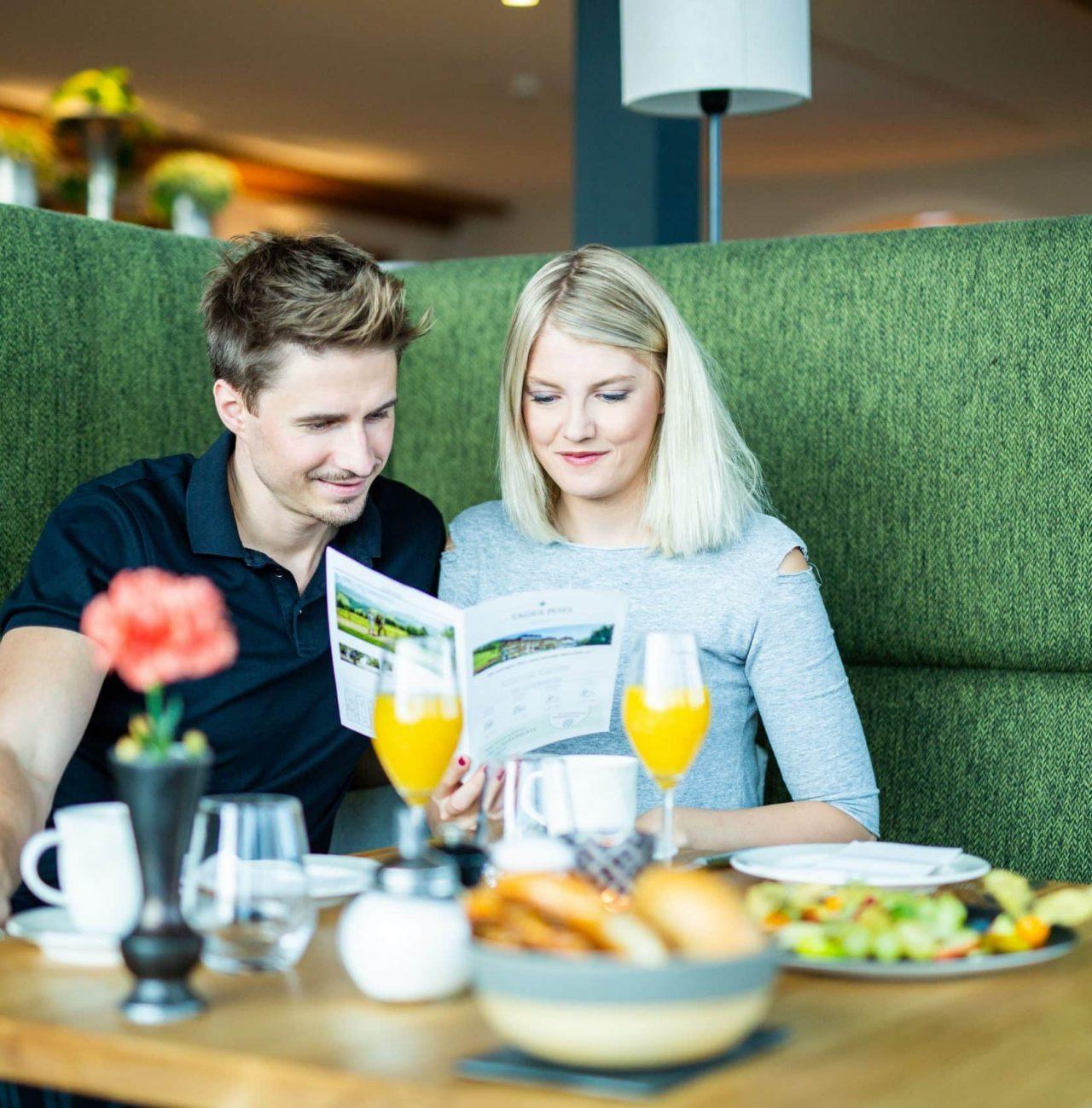 Pärchen liest Hotelzeitung von Gastfreund am Frühstückstisch im Hotel