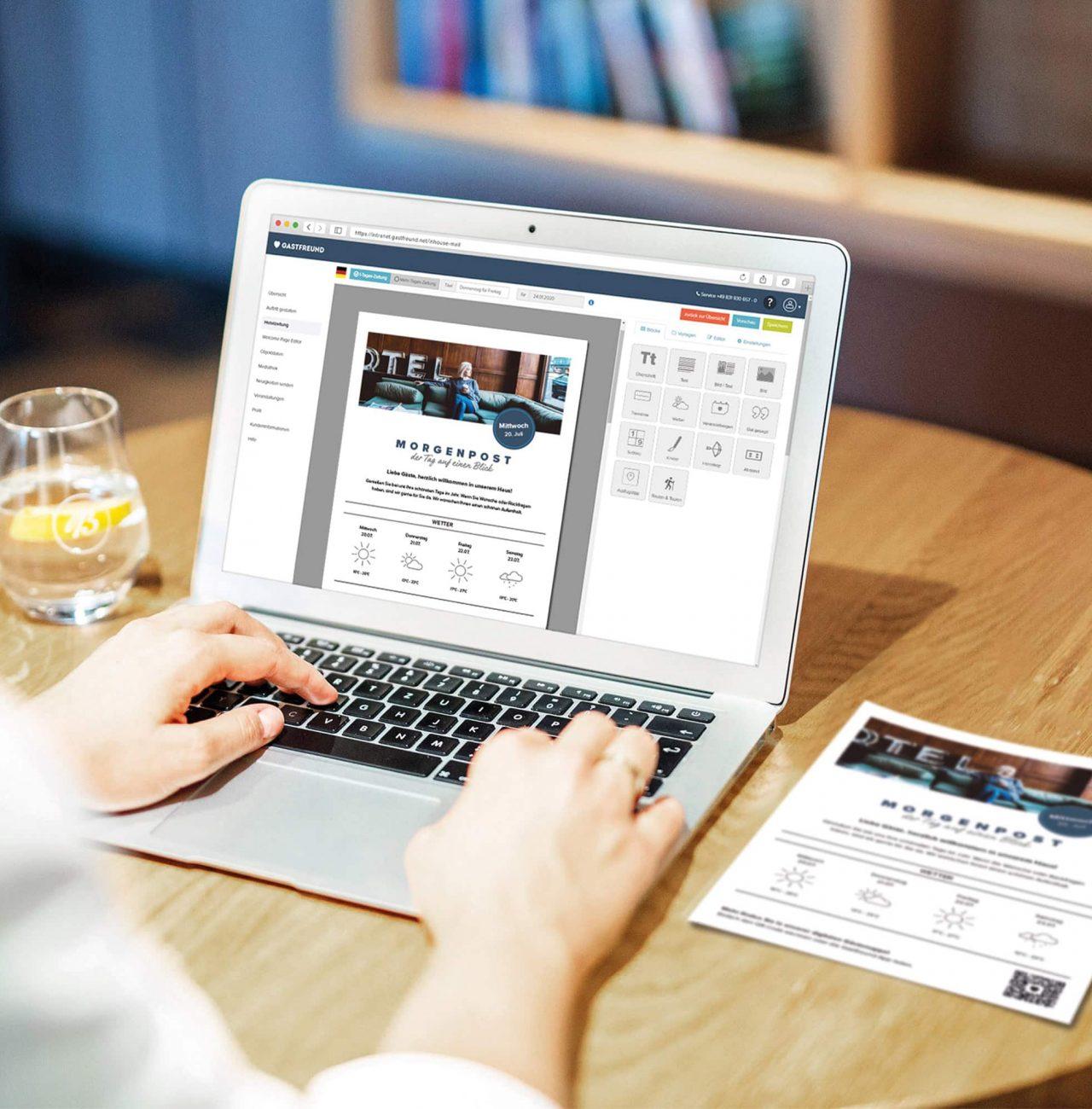 Ein Mitarbeiter des Hotels erstellt auf dem Laptop die Hotelzeitung mit dem Online-Editor mit Drag-and-Drop Funktion von Gastfreund