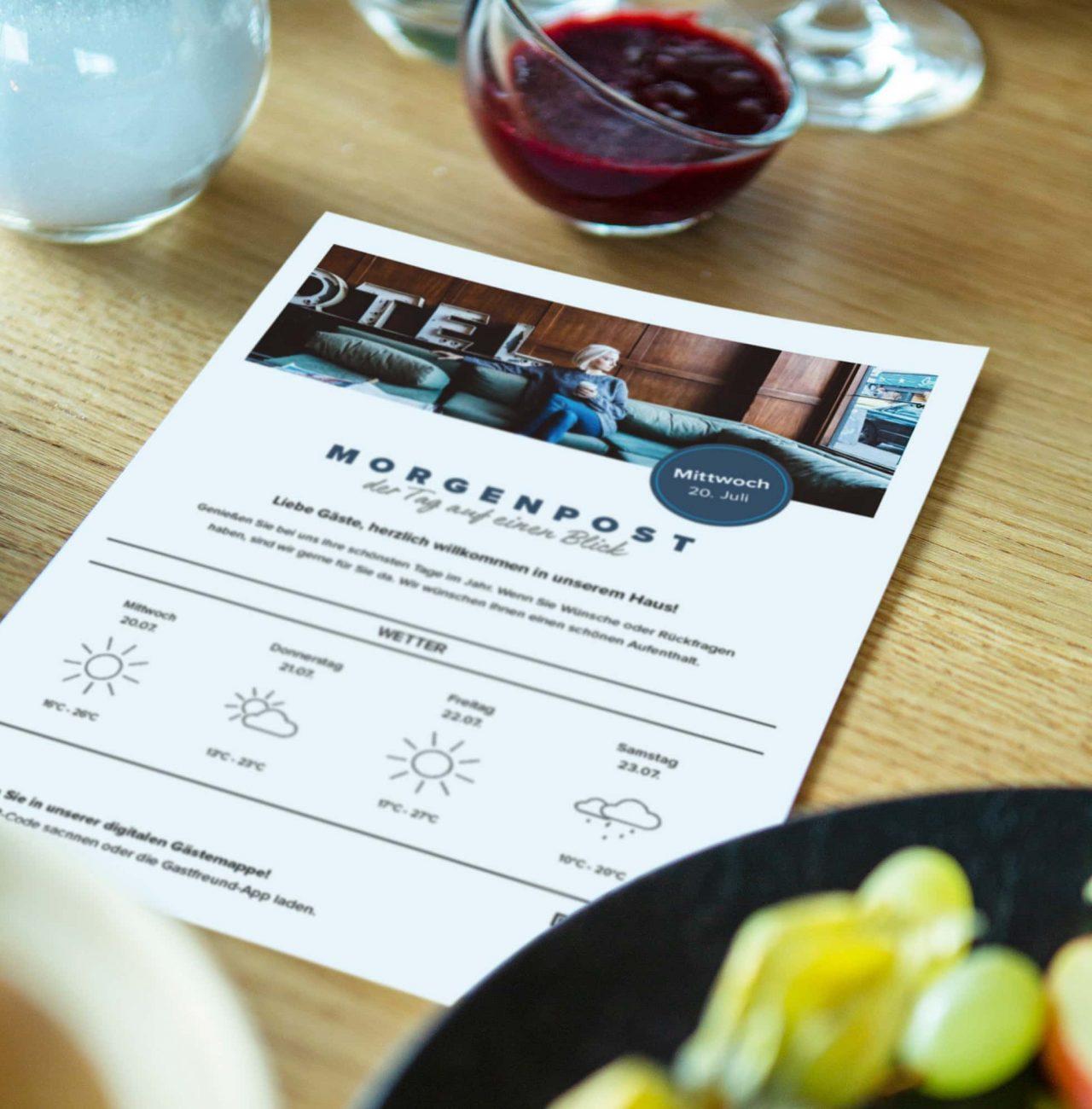 Frühstückstisch mit der ausgedruckte Hotelzeitung von Gastfreund